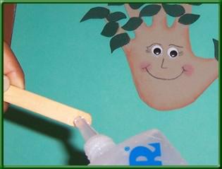 paso 14; pegar un palito de paleta al arbol con silicona liquida