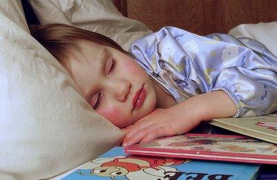 Niña durmiendo con libros