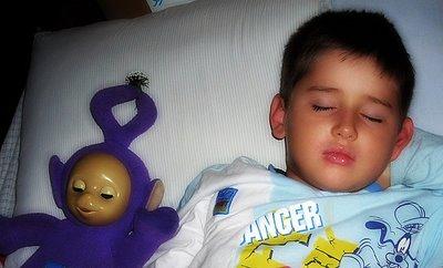 Niño durmiendo con muñeco de Teletubbies